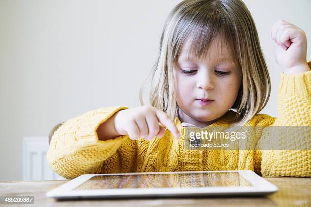Young girl at kitchen table using digital tablet