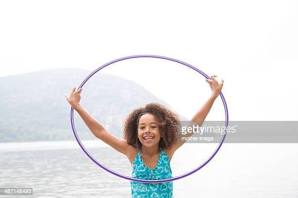 Young girl at lake with hula hoop