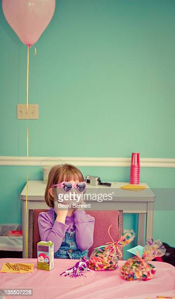 Young girl at party with treats and pink balloon