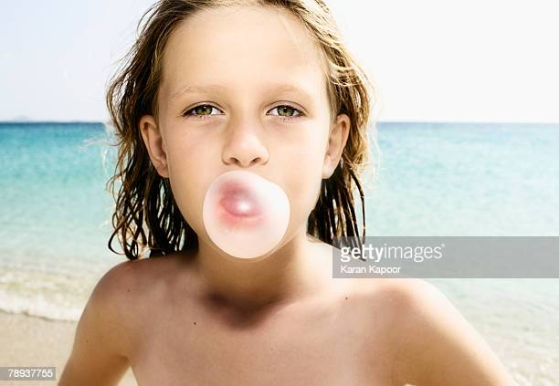 Young girl at the beach blowing a bubble with her gum.
