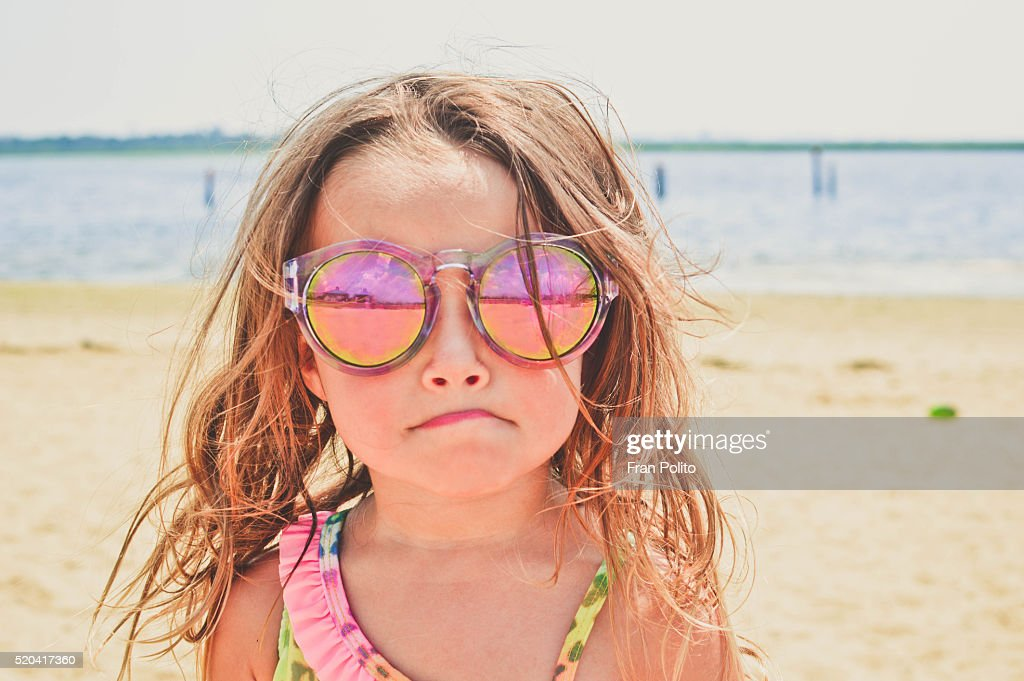 Young girl at the beach wearing sunglasses. : Stock Photo