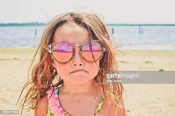 Young girl at the beach wearing sunglasses.