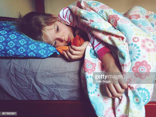 Young girl awake and relaxing in bed