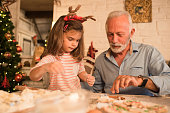 senior man helping young girl making