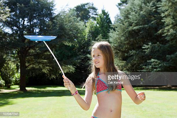 Young girl balancing a plate on stick