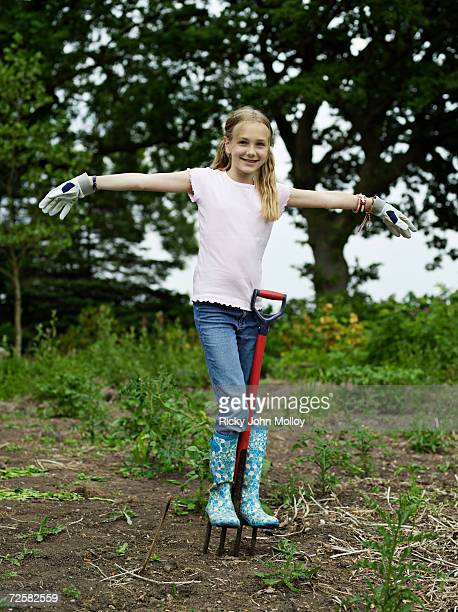Young girl (10-11) balancing on garden fork