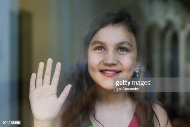 young girl behind window glass - saluting stock pictures, royalty-free photos & images
