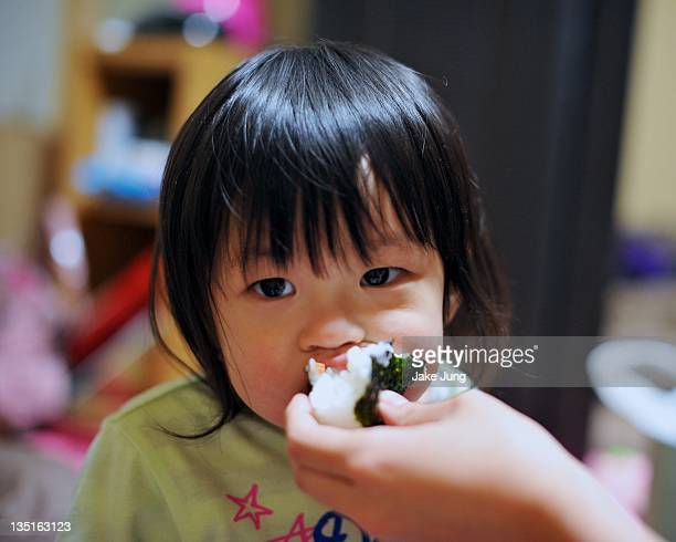 Young girl being feed a rice ball (onigiri)