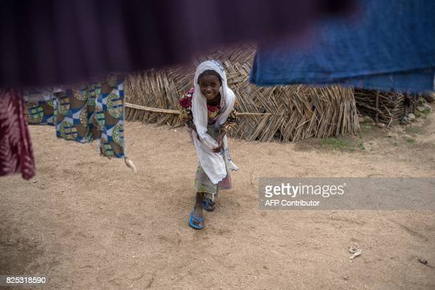 A young girl bends to see under laundry hanging in one of the InternallyDisplaced People camps in Gwoza northeastern Nigeria on August 1 2017 Boko...