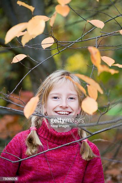 Young girl between tree branches