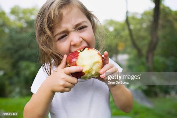 Young girl biting apple