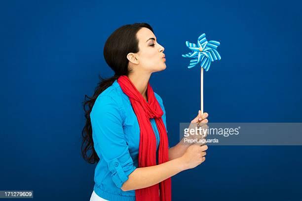 Young girl blowing a blue pinwheel