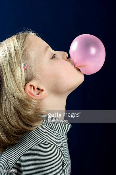 A young girl blowing a chewing gum bubble