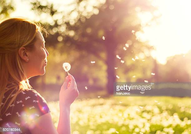 Young girl blowing away dandelion flower in nature