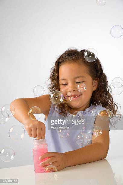 Young girl (4-6) blowing bubbles