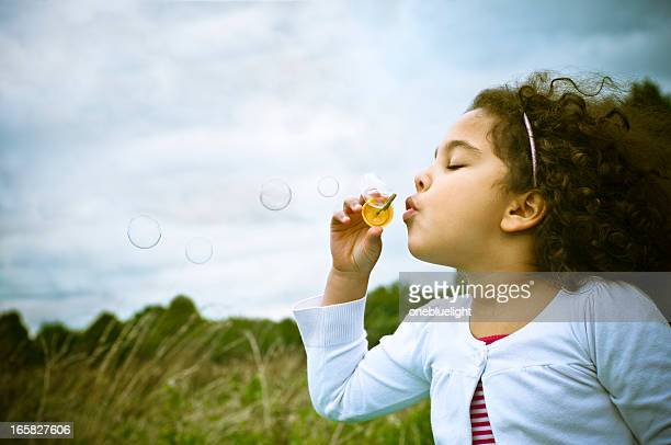 Young girl blowing bubbles with a wand