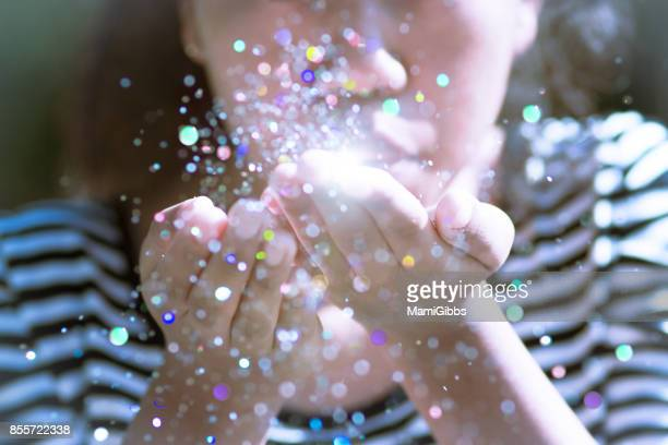 Young girl blowing colorful glitter in the air.
