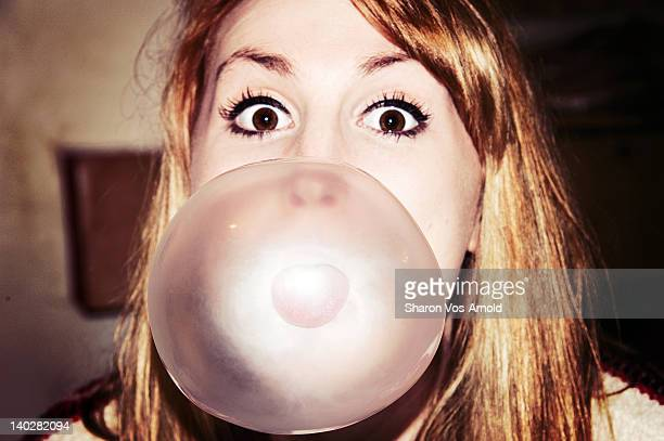 Young girl blowing huge bubble with bubble gum