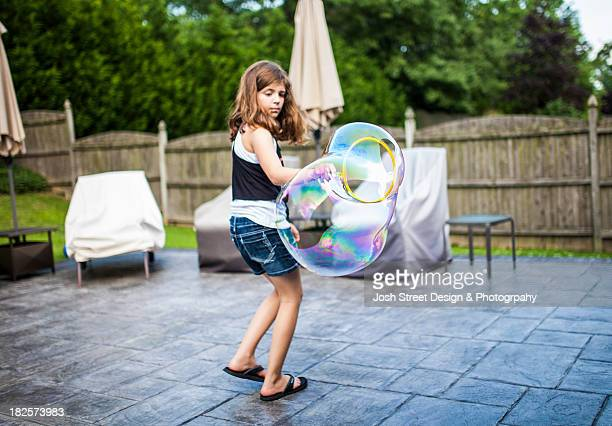 young girl blowing large bubbles - girl wear jeans and flip flops stock photos and pictures
