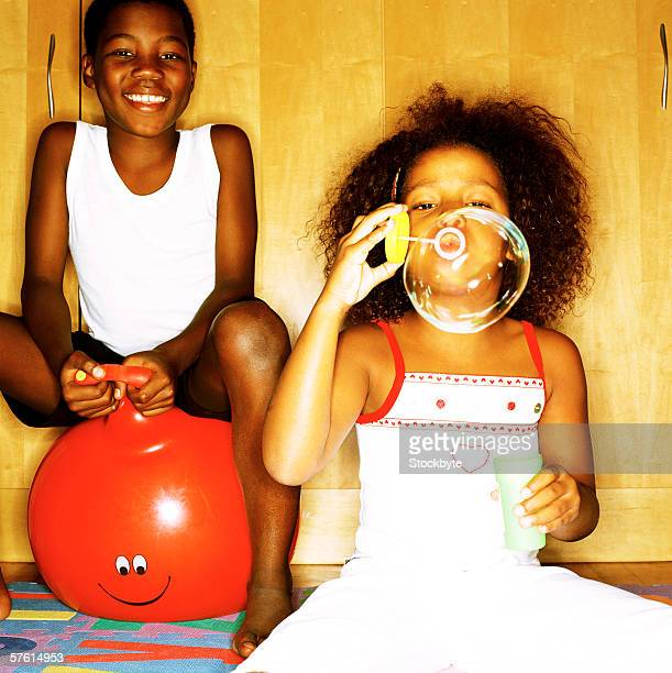 Young girl blowing soap bubbles with a young boy (6-12) sitting on a space hopper behind her