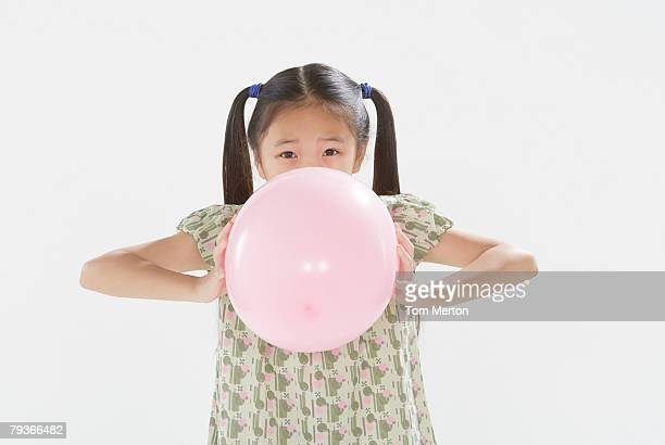 Young girl blowing up balloon indoors