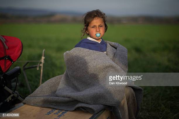 A young girl blows bubble gum while sitting by a fire at sunset at the Idomeni refugee camp on the GreekMacedonia border on March 06 2016 in Idomeni...
