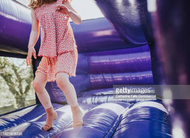 young girl bounces on a purple bouncy castle - human joint stock pictures, royalty-free photos & images
