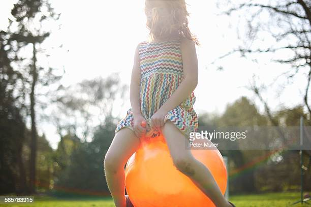 Young girl bouncing on inflatable hopper