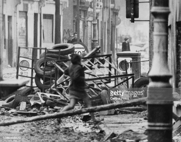 Young girl braves the stone-throwing and runs in front of a hastily-erected barricade as violence flared between local residents, organised under the...