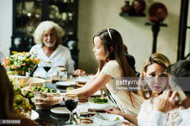 Young girl bringing food to table during multigenerational family celebration meal