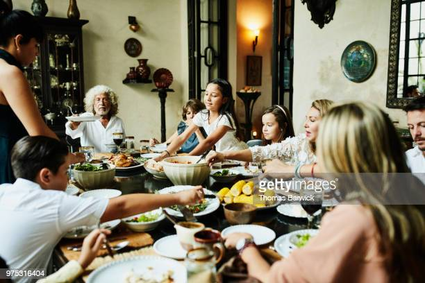 young girl bringing platter of bread to dining room table during family celebration meal - meal stock pictures, royalty-free photos & images