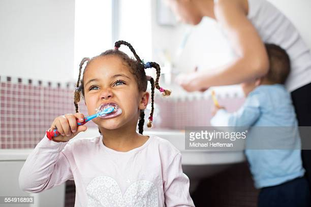 young girl brushes teeth - grooming product stock photos and pictures