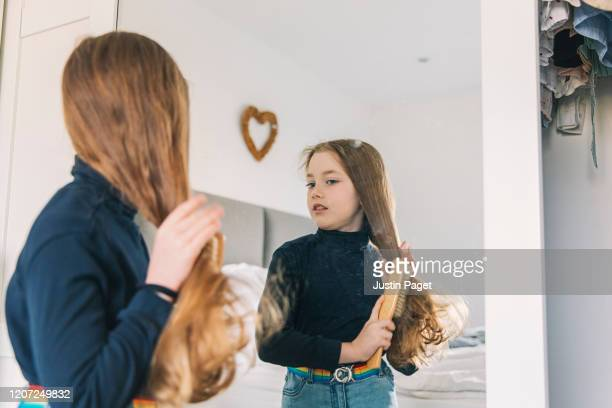 young girl brushing hair in mirror - caucasian appearance stock pictures, royalty-free photos & images