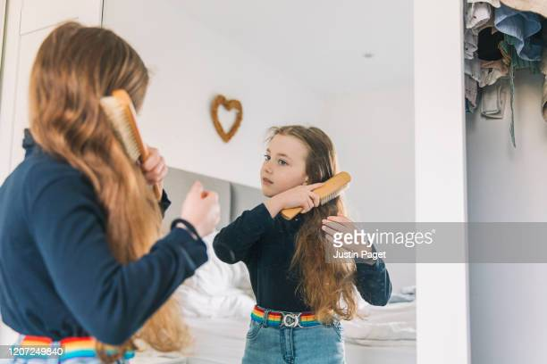 young girl brushing hair in mirror - neckline stock pictures, royalty-free photos & images