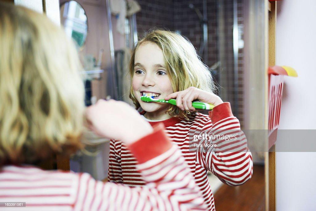 young girl brushing teeth in bathroom mirror : Stock Photo