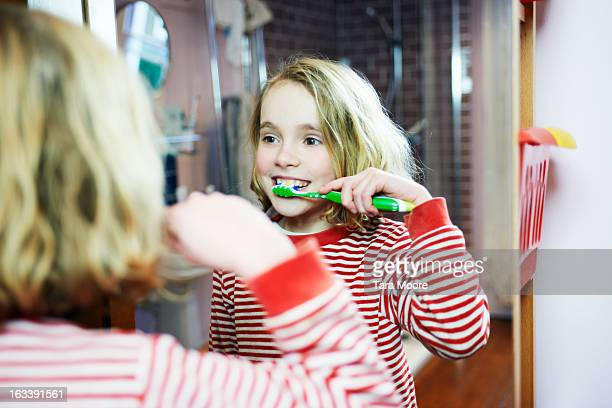 young girl brushing teeth in bathroom mirror