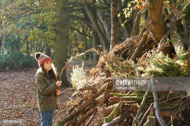 Young girl building a den in the woods
