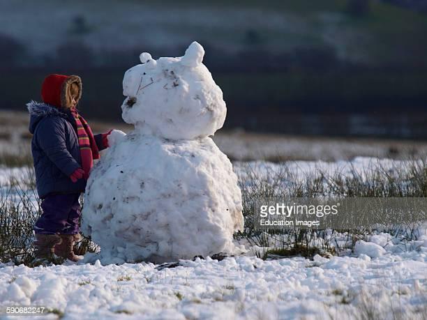 Young girl building a snowman Exmoor Somerset UK
