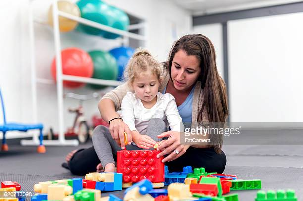 Young girl building block structure as therapist helps