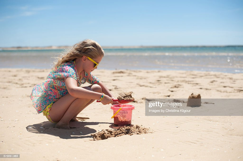Young girl building sandcastles : Stock Photo