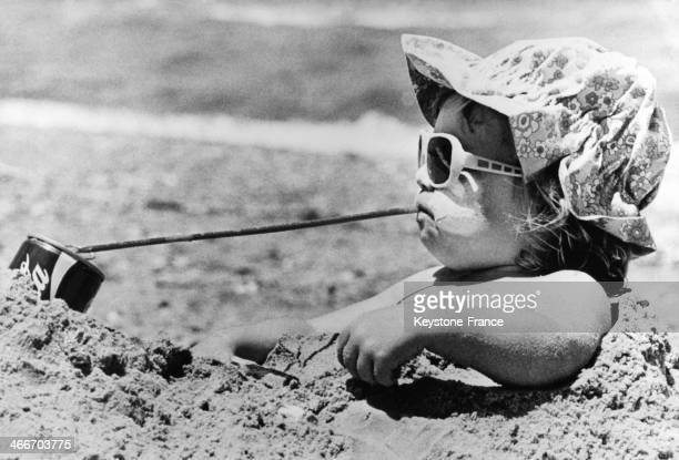 Young girl buried in beach sand having cold drink with a straw during heat wave circa 1960 in Australia