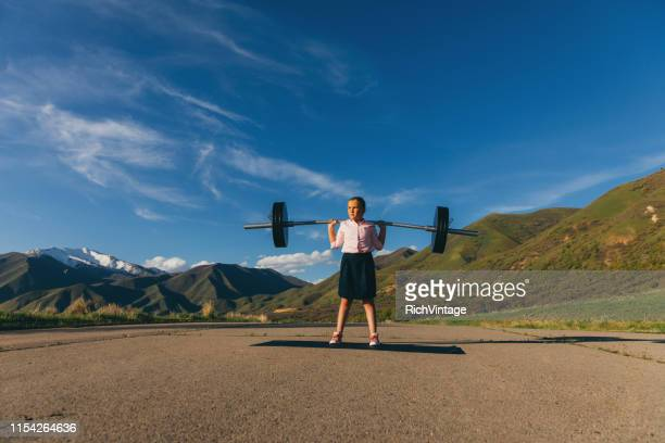 young girl businesswoman lifting weights - resilience stock photos and pictures