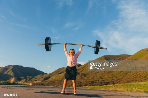 若い女の子ビジネスウーマンリフティングウェイト - kids weightlifting ストックフォトと画像