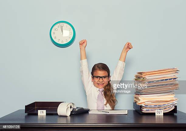 Young Girl Businesswoman Raises Arms at Office Desk