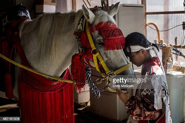 A young girl calms a horse while waiting to depart the stables to participate in the Soma Nomaoi festival on July 26 2015 in Minamisoma Japan Every...