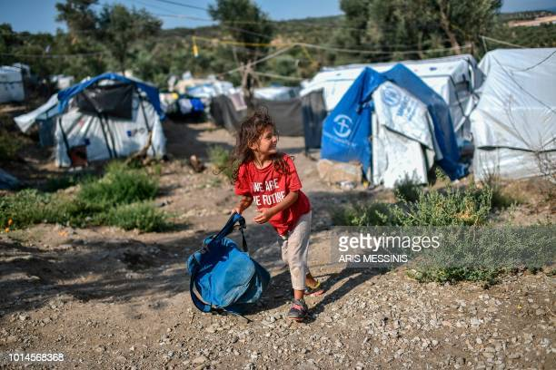 A young girl carries a backpack as she runs at a camp next to the Moria refugee camp in the island of Lesbos on August 5 2018