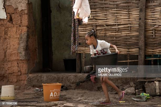 A young girl carries a bucket in the Mindara neighbourhood in Bissau on Mardi Gras on February 13 2018 / AFP PHOTO / Xaume Olleros