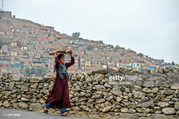 Young girl carries bread on a tray over her head at a hillside overlooking Kabul on October 6, 2019.