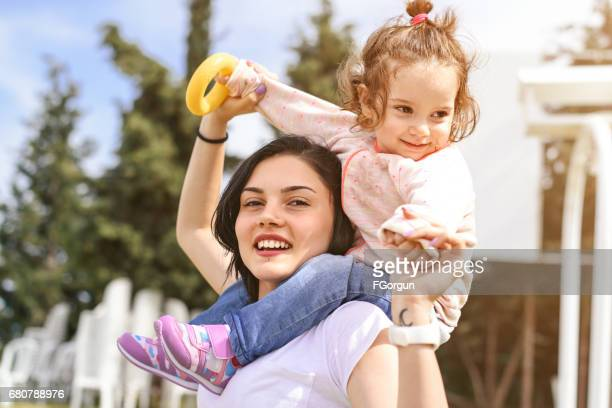 Young girl carries on the shoulders of younger sister