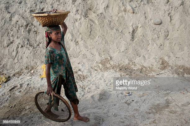 A young girl carries stones and pebbles collected from a stone quarry on the bank of Dauki river Sylhet Bangladesh January 18 2010